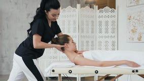 Terapeuta de sexo femenino que hace masaje del tratamiento en el cuello de la mujer joven cauc?sica almacen de video