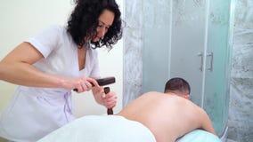 Terapeuta de sexo femenino que martilla la parte posterior masculina con el martillo tailand?s que hace a senador massage del tok metrajes