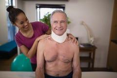 Terapeuta de sexo femenino sonriente que mira al paciente masculino mayor con el cuello del cuello Foto de archivo libre de regalías
