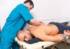 Terapeuta de sexo masculino Giving Back Massage del masaje a servir Imagen de archivo libre de regalías