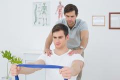 Terapeuta de sexo masculino que ayuda al hombre con ejercicios en oficina Imágenes de archivo libres de regalías