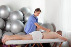 Terapeuta de sexo masculino que da masajes a la parte posterior caucásica del man s de la Edad Media Imagenes de archivo