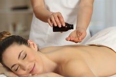 Terapeuta del masaje que aplica el producto Foto de archivo