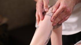 Terapeuta del masaje que da masajes al brazo con el tatuaje de la mujer atractiva joven en centro del balneario Cuidado del cuerp almacen de metraje de vídeo