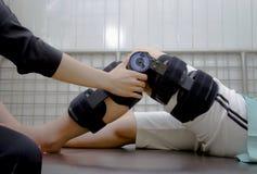 terapeuta egzamininuje cierpliwego ` s kolano z kolanowym brasem zdjęcia stock