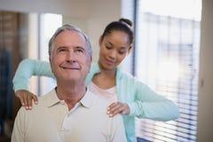 Terapeuta fêmea novo que dá a massagem do ombro ao paciente superior Fotografia de Stock Royalty Free
