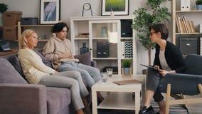 Terapeuta fêmea que escutam para serir de mãe e filho que fala durante a sessão no escritório vídeos de arquivo