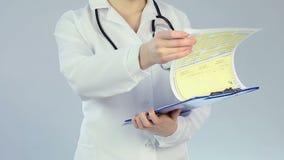 Terapeuta fêmea que verifica o informe médico do paciente, tratamento clínico qualificado vídeos de arquivo