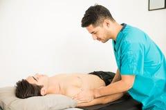 Terapeuta físico Giving Shoulder Massage al atleta In Hospita Imagen de archivo
