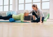Terapeuta físico que ayuda a la mujer mayor en su entrenamiento Imagen de archivo