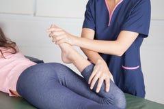 Terapeuta físico que da un tratamiento de la pierna Imagen de archivo libre de regalías