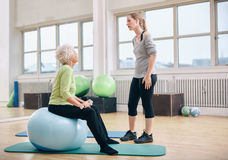 Terapeuta físico que da instrucciones a una mujer mayor en la rehabilitación Fotos de archivo