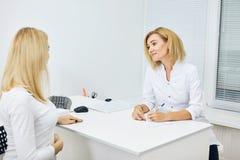 Terapeuta impressionante novo que dá recomendações a uma mulher gravida imagens de stock