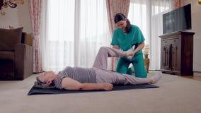 Terapeuta joven que ejercita con un más viejo paciente femenino en clínica de reposo metrajes