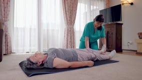 Terapeuta joven que ejercita con un m?s viejo paciente femenino en cl?nica de reposo metrajes