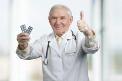 Terapeuta mayor con dos paquetes de medicina foto de archivo libre de regalías