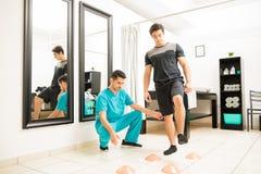 Terapeuta Motivating Male Patient a andar entre cones imagem de stock royalty free
