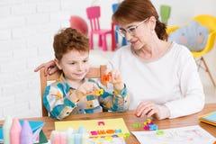 Terapeuta ocupacional e rapaz pequeno foto de stock