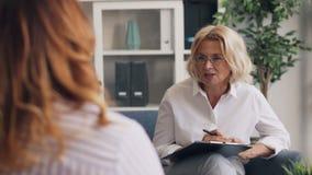 Terapeuta positivo que dá o conselho à senhora obeso durante a consulta no escritório video estoque