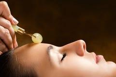 Terapeuta que aplica el rodillo del jade en cara femenina imágenes de archivo libres de regalías