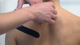Terapeuta que aplica fitas em forma de Y no ombro fêmea, dor de músculo do traumatismo do esporte filme