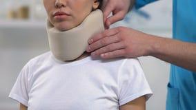 Terapeuta que aplica o colar cervical da espuma paciente fêmea, apoio médico vídeos de arquivo