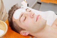 Terapeuta que aplica una mascarilla a un hombre joven hermoso en un balneario Imagen de archivo libre de regalías