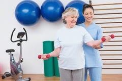Terapeuta que ayuda a pesas de gimnasia aptas de la mujer mayor Fotografía de archivo