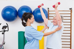 Terapeuta que ayuda a pesas de gimnasia aptas de la mujer mayor Foto de archivo libre de regalías
