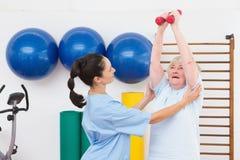 Terapeuta que ayuda a pesas de gimnasia aptas de la mujer mayor Imagen de archivo libre de regalías