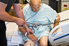 Terapeuta que controla la presión arterial paciente Imagen de archivo