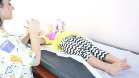 Terapeuta que dá uma massagem da mão a uma menina video estoque
