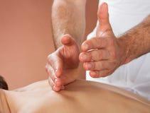 Terapeuta que da masajes a la parte posterior del cliente femenino en el balneario imágenes de archivo libres de regalías
