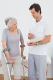 Terapeuta que discute informes con un paciente mayor discapacitado Imágenes de archivo libres de regalías