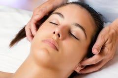 Terapeuta que faz massagens o lado das orelhas fêmeas imagens de stock