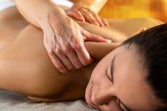 Terapeuta que faz massagens o pescoço e o ombro superiores na mulher imagens de stock