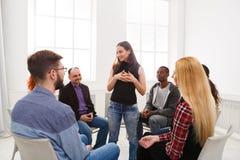 Terapeuta que habla con un grupo en la sesión de terapia fotografía de archivo