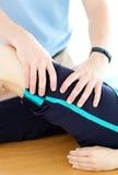 Terapeuta que hace ejercicios de la aptitud con su paciente Imágenes de archivo libres de regalías