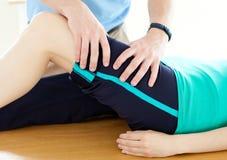 Terapeuta que hace ejercicios de la aptitud con una mujer Imagen de archivo libre de regalías