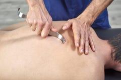 Terapeuta que hace Fibrolysis diacutaneous, de los ganchos que curan el tratamiento en el man& x27; s detr?s Medicina alternativa fotografía de archivo