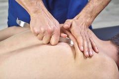 Terapeuta que hace Fibrolysis diacutaneous, de los ganchos que curan el tratamiento en el man& x27; s detr?s Medicina alternativa fotos de archivo libres de regalías