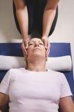Terapeuta que hace terapia del reiki a la mujer mayor imagen de archivo