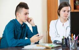 Terapeuta que recibe al paciente adolescente en clínica Imagenes de archivo