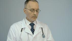 Terapeuta que usa o PC da tabuleta para verificar resultados da análise do informe médico ou do laboratório do paciente filme