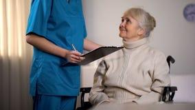 Terapeuta robi notatkom w ksi??eczkach zdrowich i egzamininuje starszej damy, szpital zdjęcia royalty free