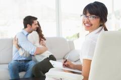 Terapeuta sonriente con los pacientes que abrazan detrás de ella Imagenes de archivo