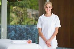 Terapeuta sonriente de la belleza que se coloca al lado de la toalla del masaje fotos de archivo