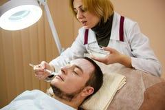 Terapeuta stosuje twarzy maskę młody człowiek obrazy stock