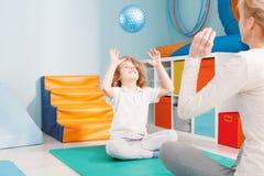 Terapeuta y muchacho que juegan la bola Foto de archivo libre de regalías