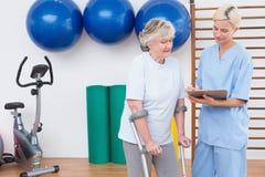 Terapeuta y mujer mayor que miran el tablero Foto de archivo libre de regalías